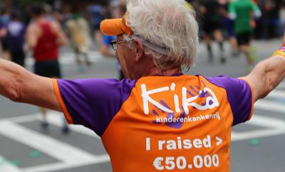 Enthousiaste ambassadeur in een KiKashirt waar op zijn rug staat dat hij 50.000 euro heeft opgehaald