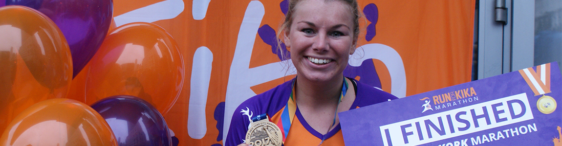 Blije deelneemster met medaille, KiKa shirt, paarse/ oranje ballonnen en bord met 'I finished'.