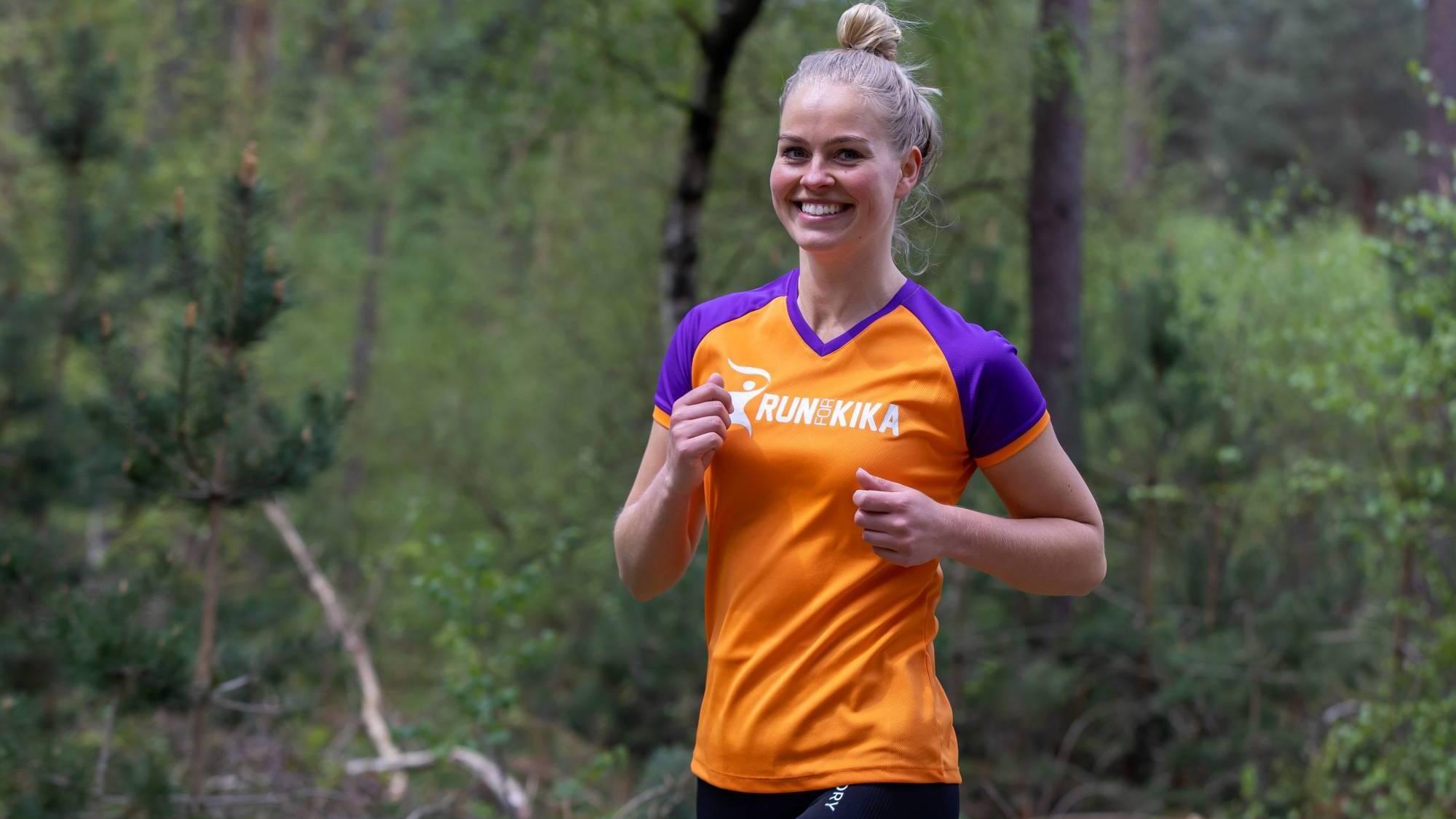 Deelnemers Veluwe Marathon rennen over brug in het Nederlands Openluchtmuseum.