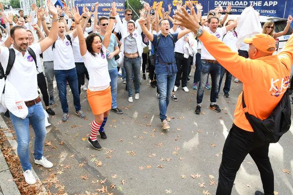 juichende deelnemers met handen omhoog in witte KiKa polo en begeleider.