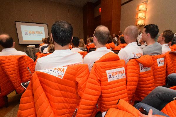 deelnemersbijeenkomst, kijken naar een presentatie met oranje KiKa jassen en witte KiKa polo's
